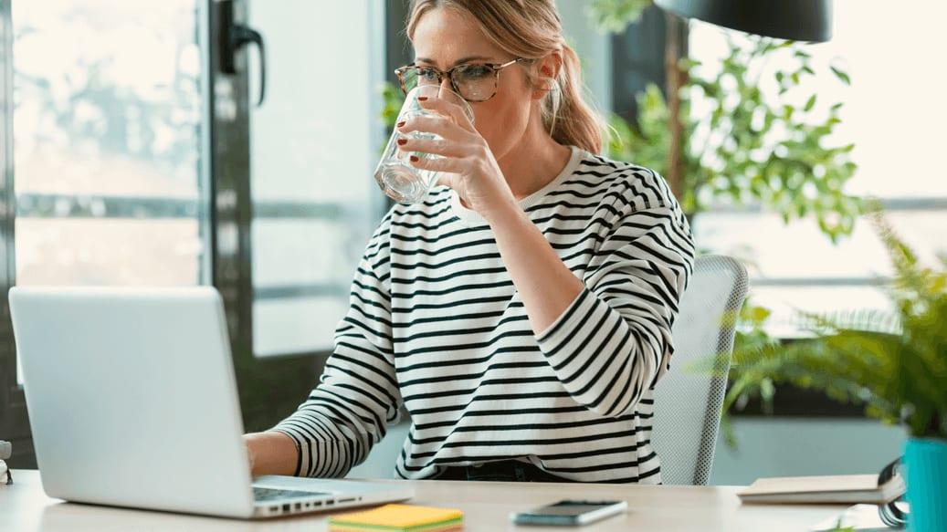 Kollega drikker vand ved pc