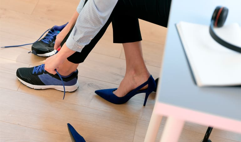 Medarbejder skifter sko ved skrivebord
