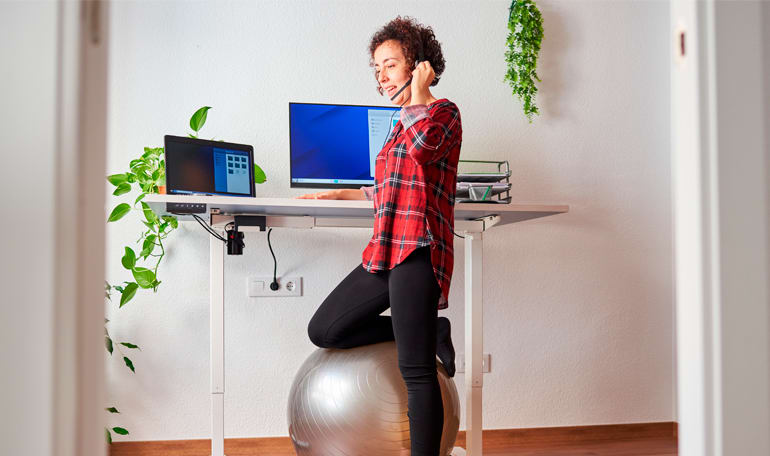 Kollega står med massagebold ved skrivebord