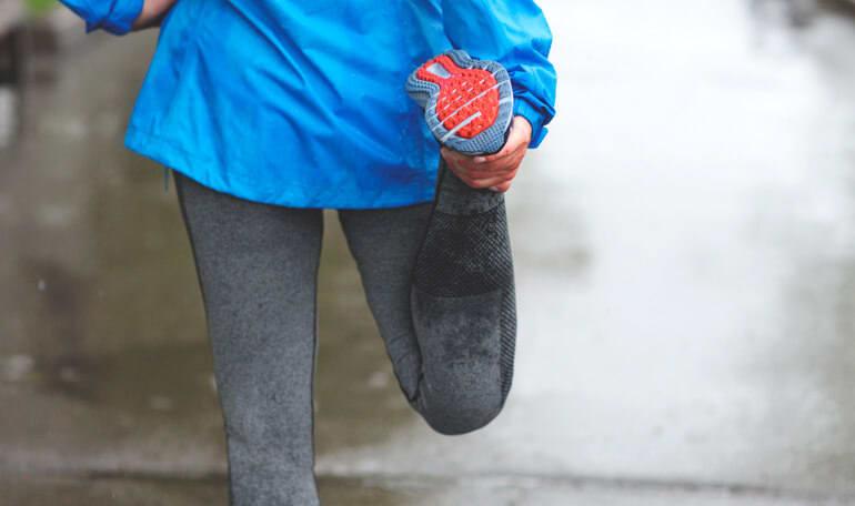Person i træningstøj strækker ud i regnvejr
