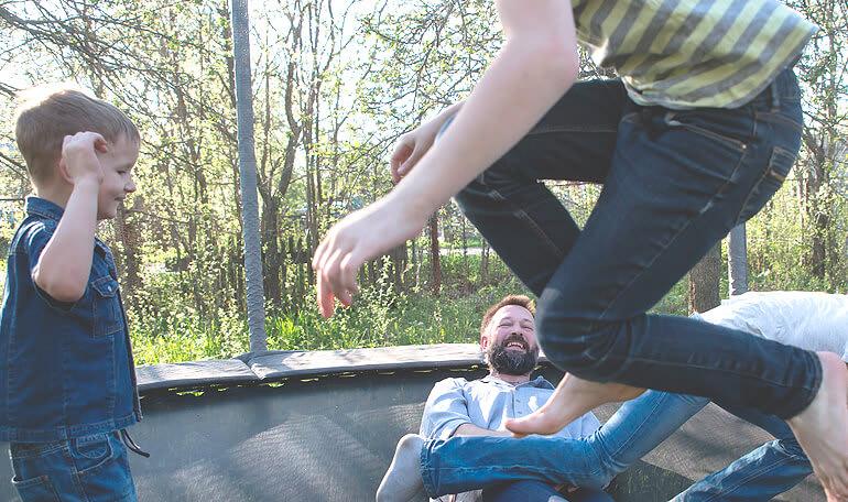 Familie leger på trampolin