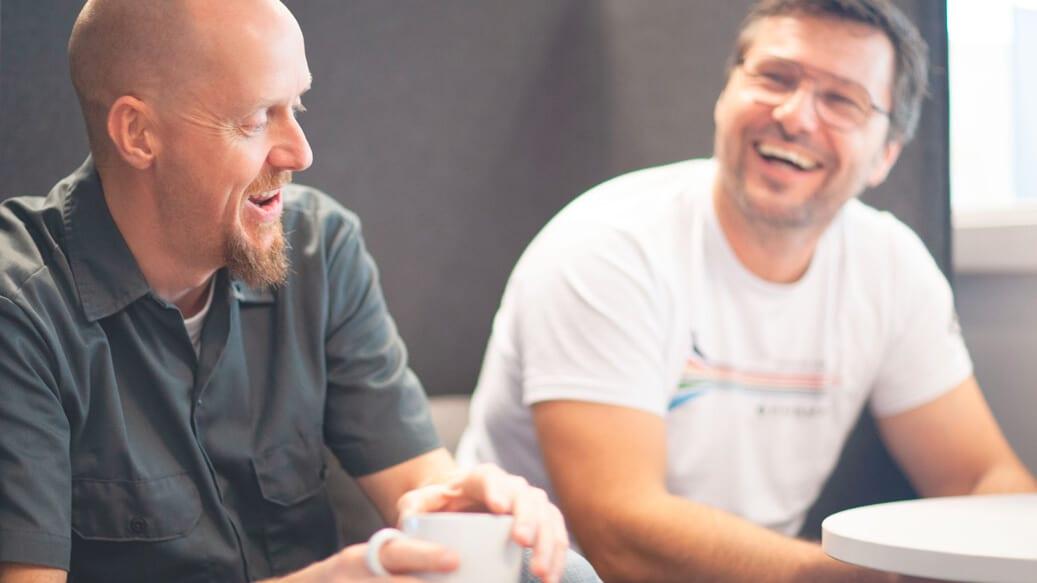 To mandlige kolleger taler og griner på arbejdspladsen