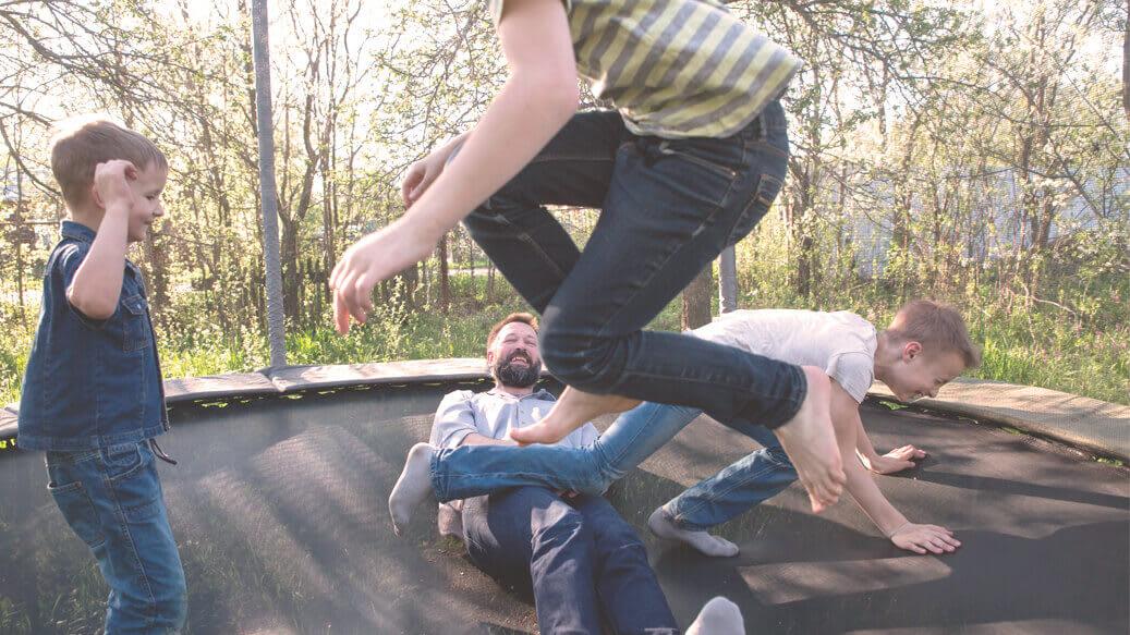 Far og børn på trampolin har det sjovt