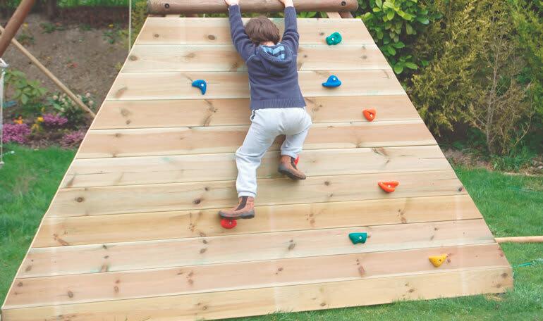 Barn klatrer på klatrevæg i have