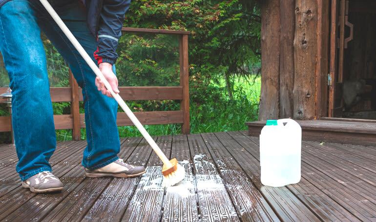 Person rengør træterrasse