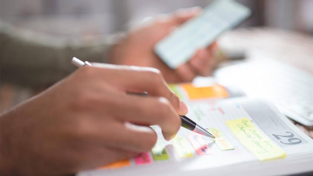 Person med mobiltelefon i haand skriver i sin kalender