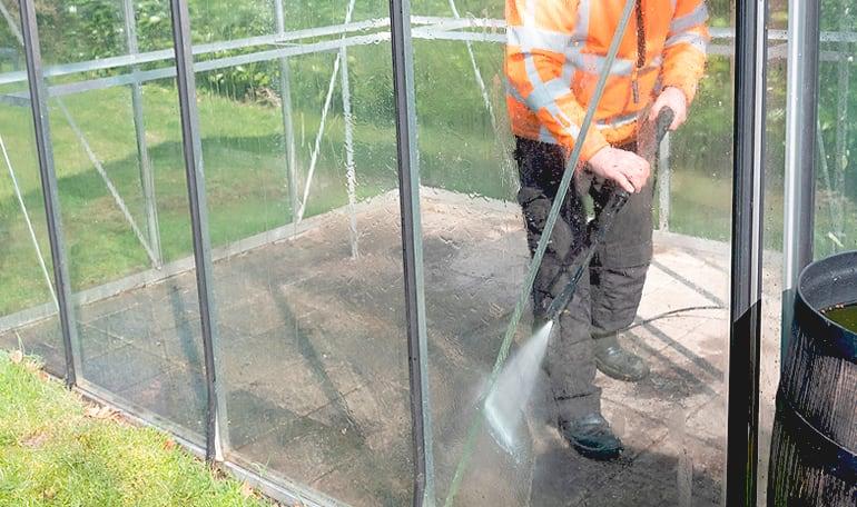 Person gør drivhus rent med højtryksrenser